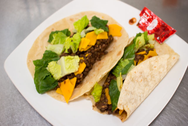 Vegan Lentil Tacos with flour tortillas, Daiya vegan cheddar, lettuce, and Fire sauce